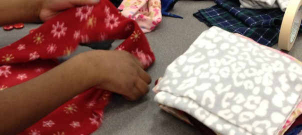 hands working on creating fleece scarves