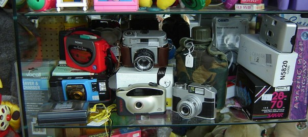 Decorative image of cameras and toys in the window of a UK charity shop. Attribution at bottom of blog post.